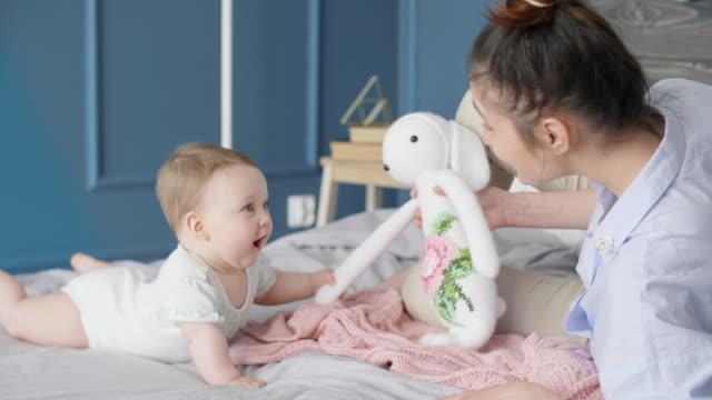 kvinna leker med dotter hemma - ligga på mage bildbanksvideor och videomaterial från bakom kulisserna