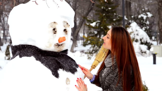 Woman playing with snowman video