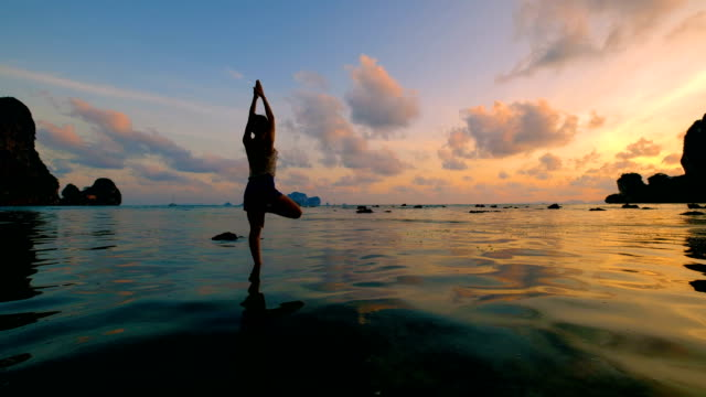 Woman playing Yoga at the beach in sunset sky video