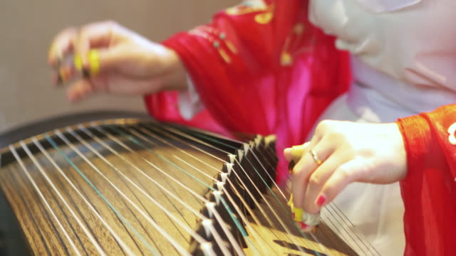 woman plays a traditional Chinese instrument, the beautiful and melodic Gu Zhen