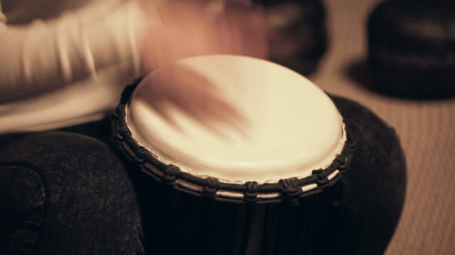 Woman plays fast beat on djembe, traditional African drum video