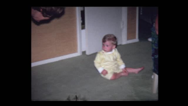 1971 woman plays peekaboo with infant grandson - hotel reception filmów i materiałów b-roll