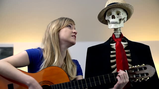 Woman plays the guitar passionately to skeleton Woman plays the acoustic guitar and sings songs to entertain the sitting skeleton animal skeleton stock videos & royalty-free footage
