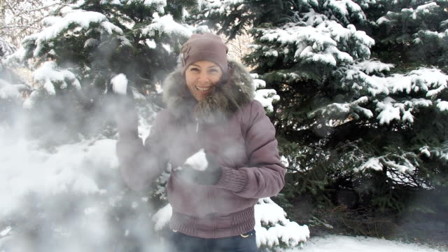 A woman plays with snowballs. A woman plays with snowballs. The girl throws snow at the camera. christmas fun stock videos & royalty-free footage