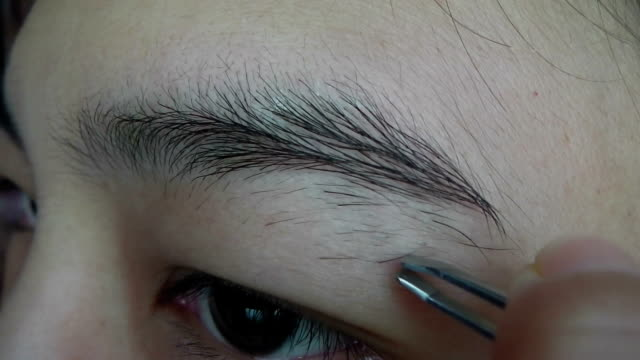 vídeos de stock e filmes b-roll de woman plucking her eyebrows - puxar cabelos