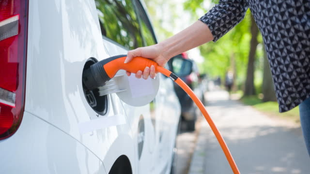 Woman plugging in electric car to charging station at an electric plug-in vehicle preferred parking in outskirts Woman plugging in electric car to electric vehicle charging station at an electric plug-in vehicle preferred parking in the green outskirts refueling stock videos & royalty-free footage