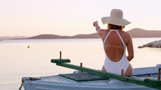 WS Woman pointing at somewhere while sitting on a boat video