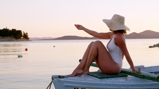 LS Woman pointing at somewhere while sitting on a boat video