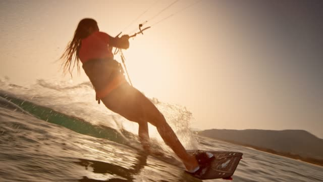SLO MO Woman popping into the air on her kiteboard at sunset
