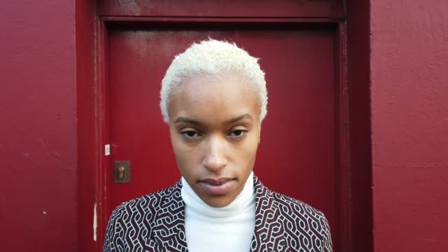 Woman portrait against a red door in London - video