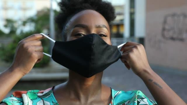 Woman portrait wearing a black cloth face mask video