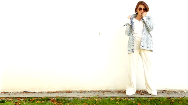 Woman posing in front of white wall smiling