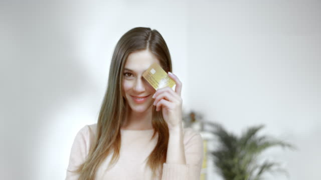 SLO MO Woman posing with credit card in her hand Slow motion medium shot of a beautiful woman posing with a credit card in her hand, looking at the camera and smiling. gold card stock videos & royalty-free footage