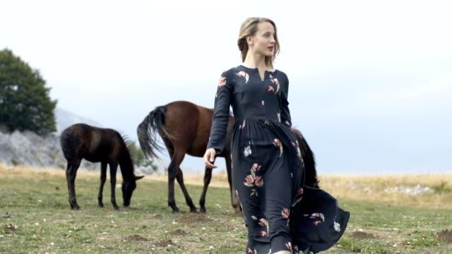 vídeos y material grabado en eventos de stock de mujer posando con los caballos. paisaje de montaña - moda de otoño