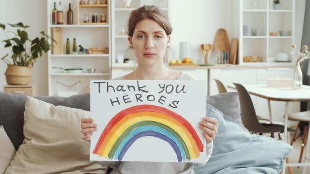 Woman Posing with Poster with «NHS thank you heroes» Sign and Rainbow Young Caucasian woman showing handmade poster rainbow and «NHS thank you heroes» inscription and looking at camera while sitting on couch at home during coronavirus quarantine thank you stock videos & royalty-free footage