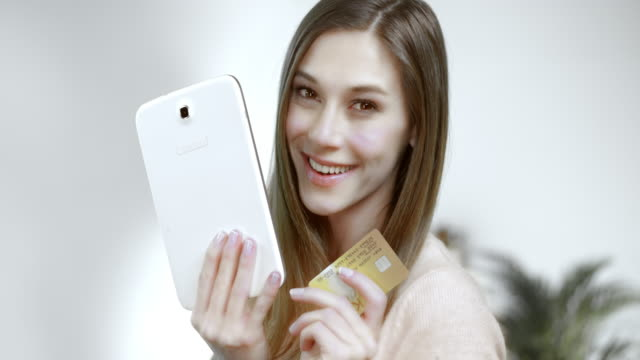 SLO MO Woman posing with tablet and credit card Slow motion medium shot of a beautiful woman smiling into the camera holding her credit card and a tablet. gold card stock videos & royalty-free footage
