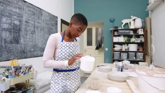Woman pottery artisan making ceramic pot in studio