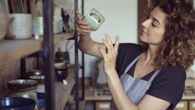artista di ceramiche donna che lavora nel suo studio d'arte - artigiano video stock e b–roll