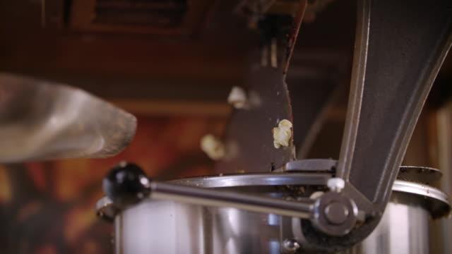 vídeos de stock, filmes e b-roll de mulher derramando milho miolo na pipoqueira. processo de produção de pipoca - balde pipoca