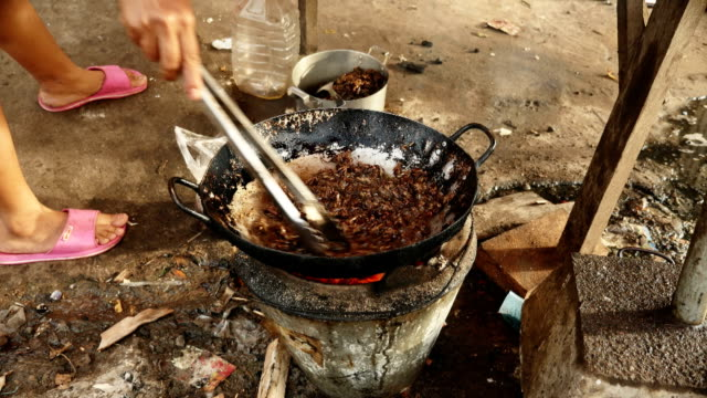 Woman pouring fried oil into a wok with frying grasshoppers video