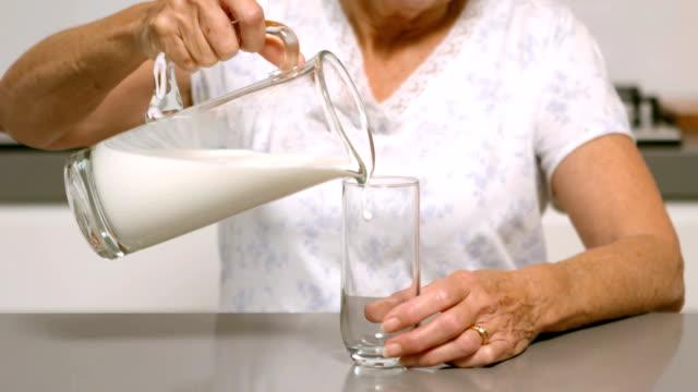 女性のグラスに注ぐミルクのキッチン - キッチンカウンター点の映像素材/bロール