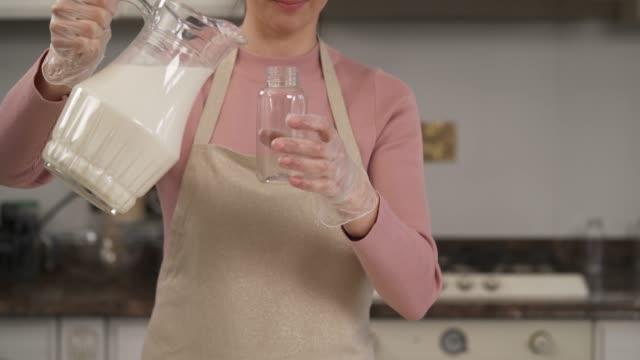 eine frau gießt milch aus einem glaskrug in die flasche. mandelmilch. vegetarisches, veganes produkt, gesundes ernährungskonzept - milchkrug stock-videos und b-roll-filmmaterial