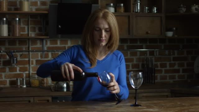 vídeos de stock, filmes e b-roll de mulher derramando vinho vermelho em copos na cozinha - comida feita em casa