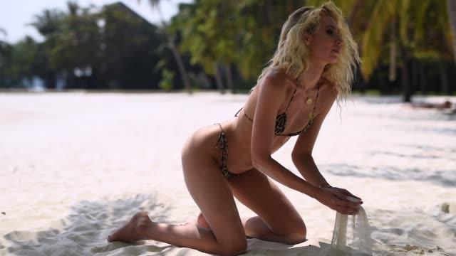 vídeos de stock e filmes b-roll de woman pouring sand running through fingers slow motion at the beach with sun flare - mulher deixar ir