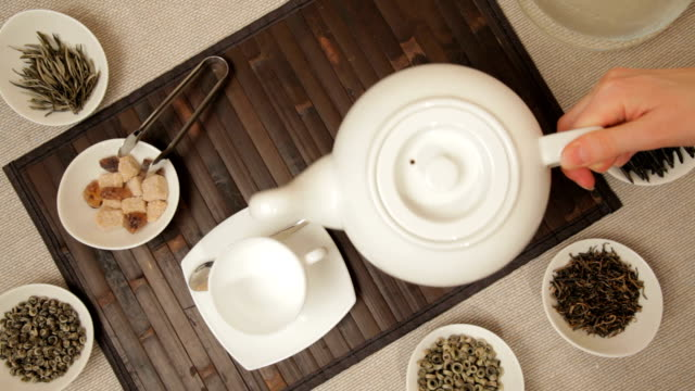 stockvideo's en b-roll-footage met woman pouring tea into cup from teapot - camelia white