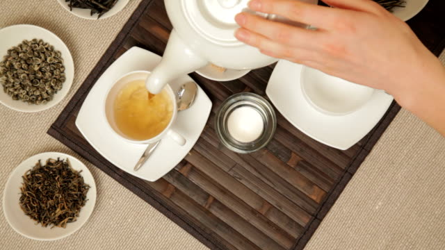 stockvideo's en b-roll-footage met woman pouring tea into cups from teapot - camelia white