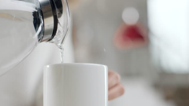 woman pouring water in mug - bollente video stock e b–roll