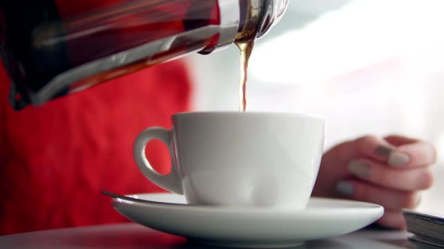 woman pours tea into a cup video