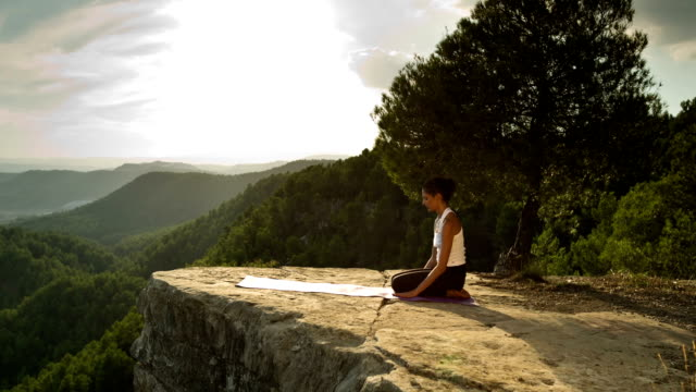 woman practices yoga outdoors video