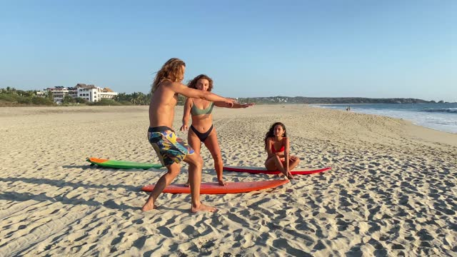 Woman practicing balance on the surfboard and friends watching her