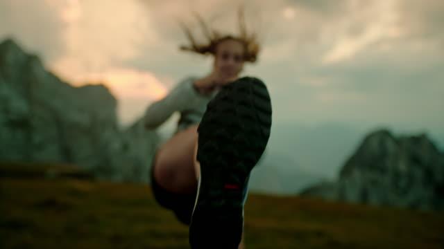 SLO MO Woman practicing martial arts kicks in mountains
