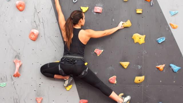 vídeos y material grabado en eventos de stock de mujer practicando escalada en pared artificial en el interior. concepto de estilo de vida y bloque activo - escalada en rocas