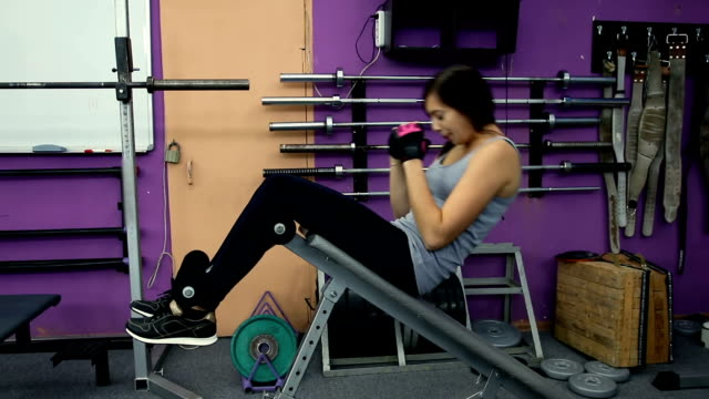 Woman practicing sit-ups on exercise machines at the gym. Woman exercise sit-ups on the weight bench video
