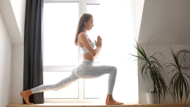 woman practicing warrior yoga pose indoors against window background - cuffie wireless video stock e b–roll