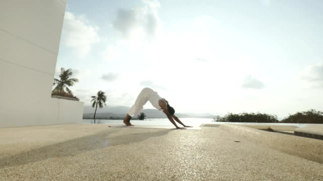 Woman practicing yoga asanas on outdoor terrace with panoramic view video