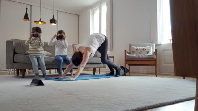 Frau übt Yoga zu Hause mit ihren Kindern während der Quarantäne – Video