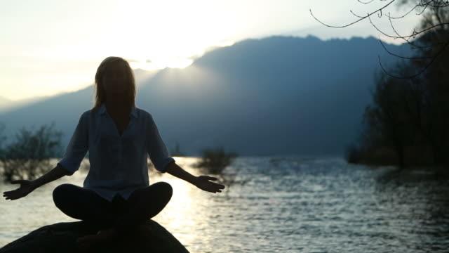 donna praticare yoga al tramonto - braccio umano video stock e b–roll