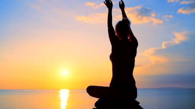HD DOLLY: Woman Practicing Yoga At Sunset
