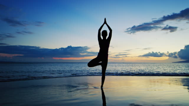 Woman Practicing Yoga at Sunset video
