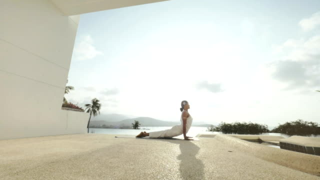 Woman practicing yoga exercises on outdoor terrace with sea and hill landscape video