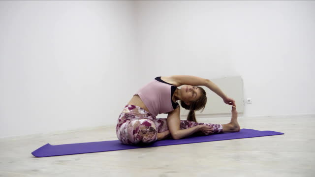 Woman practicing yoga fitness exercise in a white studio indoors video