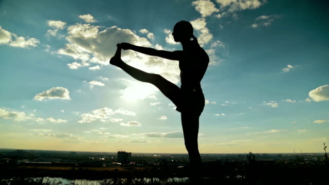 Woman practicing yoga in the park at sunset Silhouette of sporty woman practicing yoga in the park at sunset - utthita hasta padangushthasana. Sunset light. Freedom, health and yoga concept mental wellbeing stock videos & royalty-free footage