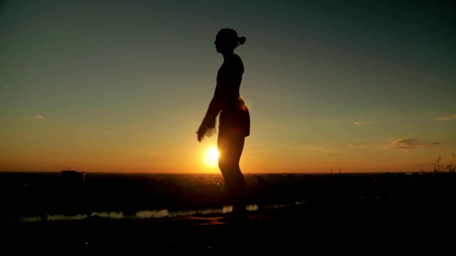 Woman practicing yoga in the park at sunset Silhouette of sporty woman practicing yoga in the park at sunset. Sunset light, sun lens flares, golden hour. Freedom, health and yoga concept mental wellbeing stock videos & royalty-free footage