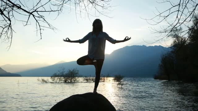 donna praticare yoga si sposta su una roccia - braccio umano video stock e b–roll