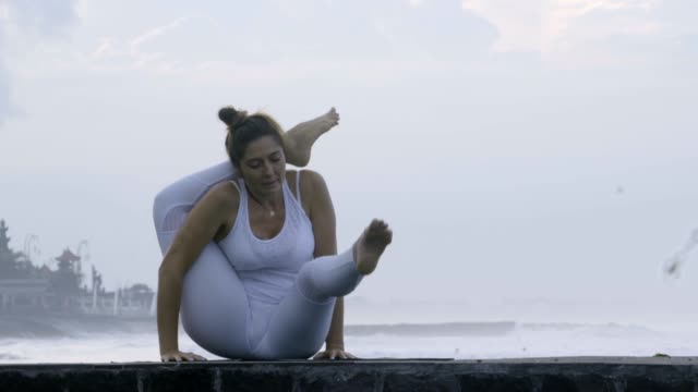 Woman Practicing Yoga on Pier