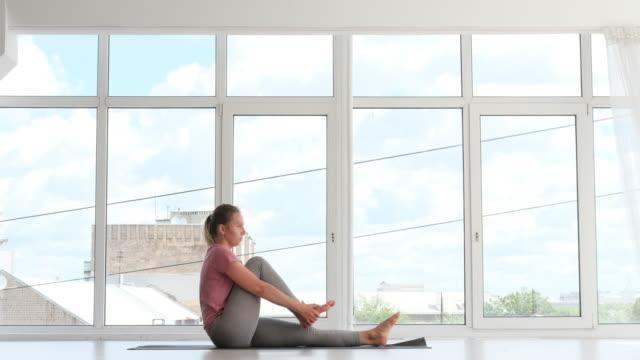 vídeos de stock, filmes e b-roll de mulher praticando pose de ioga em estúdio de fitness - comodidades para lazer